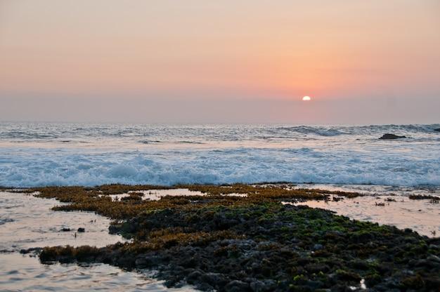 Закат на пляже танах лот в бали индонезия вечером