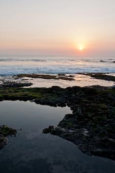 Закат на пляже танах лот в бали индонезия море вечером