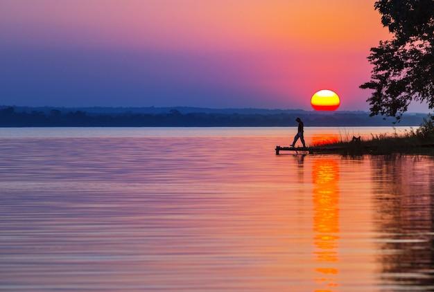 日没の秋の自然の風景で湖の夕日のシーン