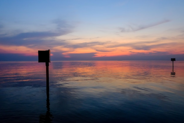 Sunset scene with warning marking steel pole in the sea, twilight time.