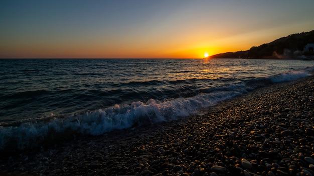 Sunset at sea. pebble beach, waves
