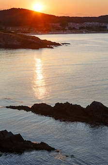 Sunset sea rocky coast view with sun track on water surface and town beach.