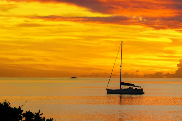 Sunset in sea and sailing yacht silhouette
