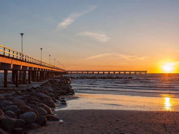 Вид на море на закате с пирсом и камнями