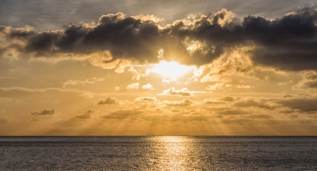 Sunset over the sea with the sun rays through the clouds