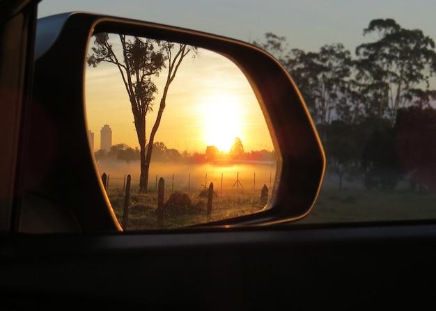 車のバックミラーから見た夕日