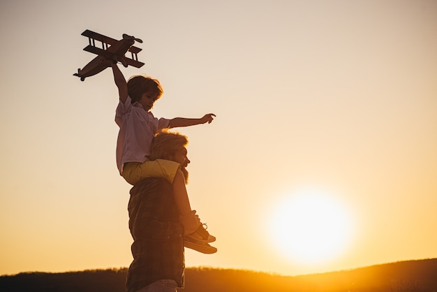 Sunset silhouette of happy father and child son with airplane dreams of traveling. father carrying his son on shoulders.