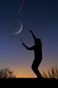 Sunset silhouette of a man with drumsticks,  interaction with moon