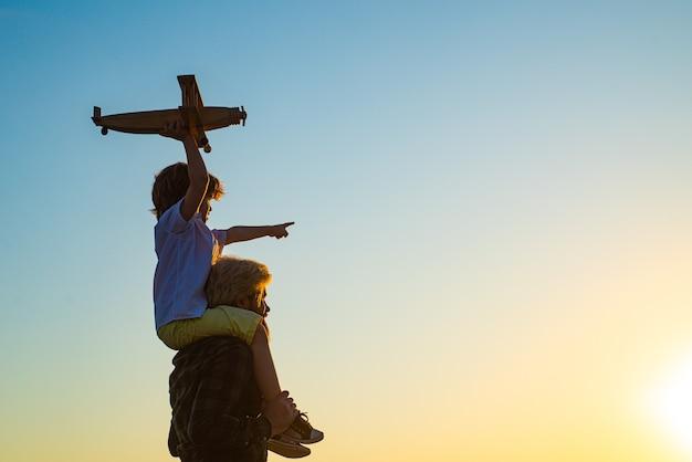旅行の飛行機の夢を持つ幸せな父と子供の息子の夕日のシルエット。幸せな男の子の子。