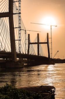 Sunset silhouette of widest in the world suspension bridge al faraj during construction