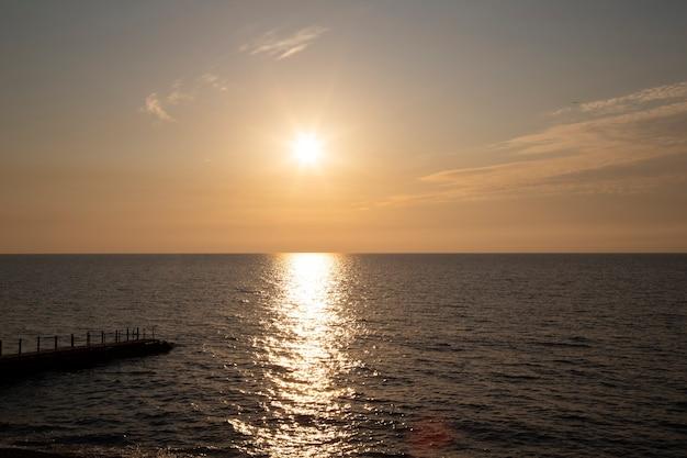 サンセットシルバーベージュトーン。夕焼け空と雲の切れ間から太陽が降り注ぐ穏やかな海。瞑想の海と空の背景。静かな海の景色。水上の地平線。