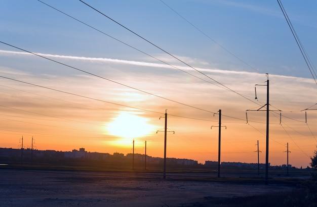 마을 위의 일몰 하늘과 고압 송전선