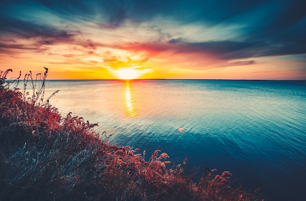Sunset sky background natural sunset sunrise over ocean bright dramatic sky and blue water colorful