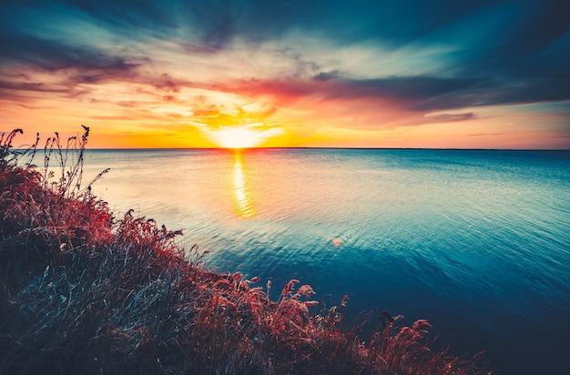 夕焼け空の背景海の上の自然な日没の日の出明るい劇的な空と青い水カラフル