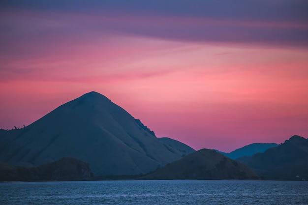 일몰 하늘, 산, 바다. 풍경. 인도네시아 코모도. 산과 태평양 너머로 멋진 화려한 일몰. 인도네시아 코모도 국립공원. 보라색, 보라색, 파란색 및 색상의 스플래시.