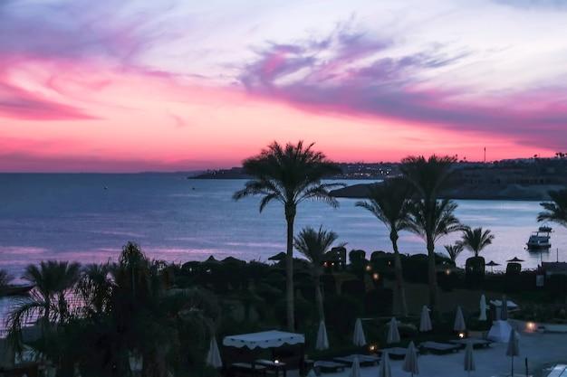 Закат небо над морем и пляж с пальмами в отелях приморского курорта на красном море