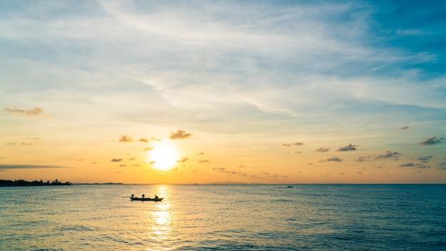 夕方の海に沈む夕日と漁船