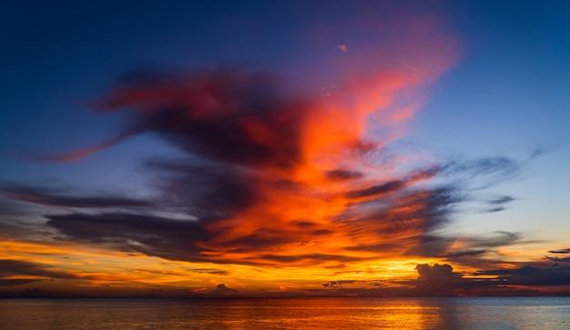 Закатное небо над морем вечером в сумерках с величественными оранжевыми облаками солнечного света после заката на фоне заката.
