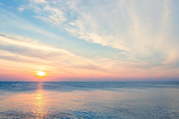 Закатное небо над морем вечером с красочными облаками оранжевый солнечный свет Premium Фотографии
