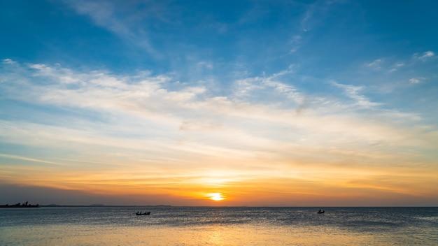 일몰과 아름다운 구름 솜털에서 화려한 오렌지 햇빛과 저녁에 바다 일몰 하늘.