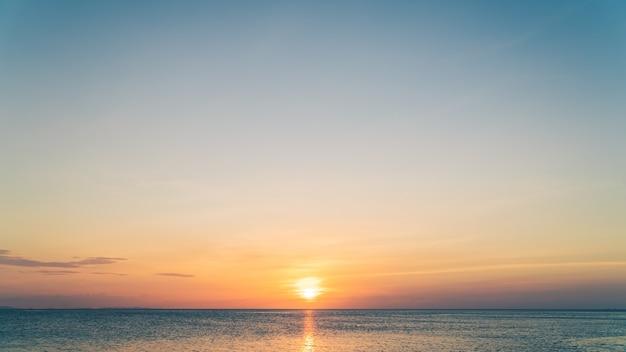 Закатное небо над морем вечером с красочным оранжевым солнечным светом на фоне заката неба