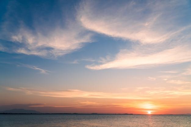カラフルな日没のオレンジ色の日光、夕暮れの空と夕方の海に沈む夕日。