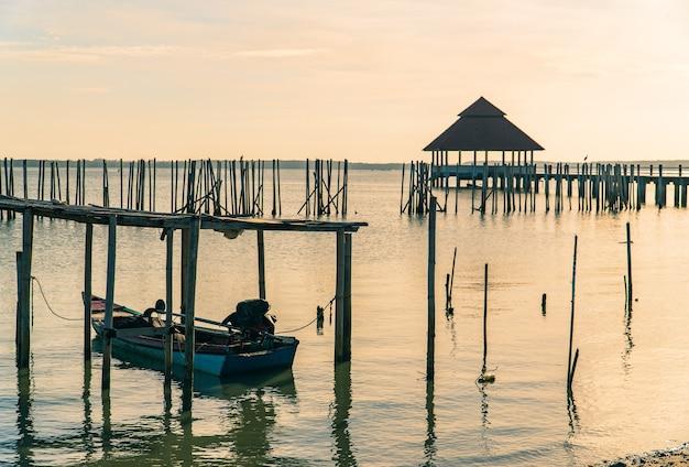 朝の海に沈む夕日とウォーキングブリッジと漁船の前景に選択的な公共パビリオン
