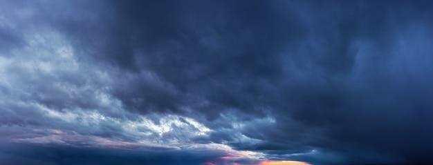 暗い雨雲と夕焼け空のパノラマ。