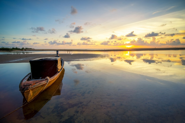 Sunset sky and sea landscape with wooden boats.