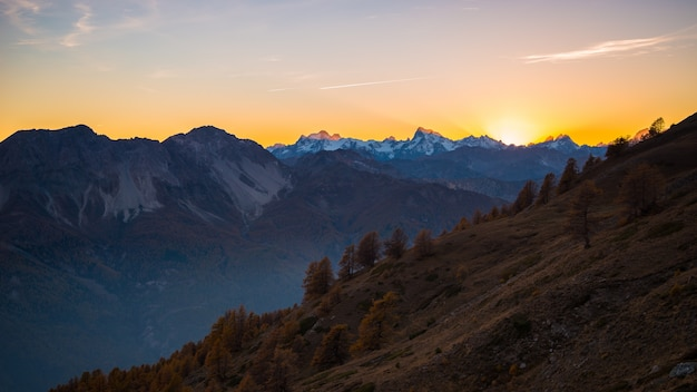 Sunset sky over snocapped mountain peak on the alps