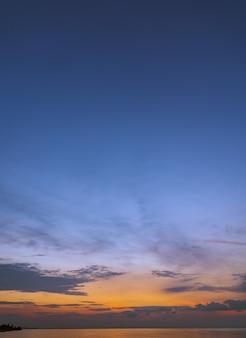 夕方の海に垂直な夕焼け空と夕暮れの色とりどりの日光