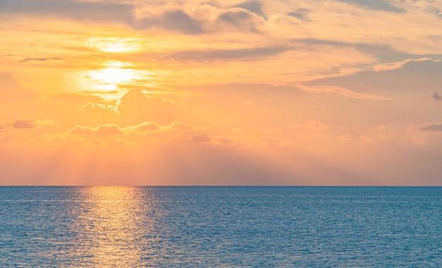 カラフルな日光と夕方の海に垂直な夕日の空