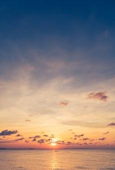 저녁에 바다 위에 수직 일몰 하늘