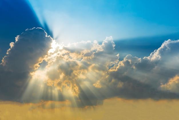 雲と太陽の光線を伴う夕焼けの空。自然の背景。奇跡、希望、または素晴らしい自然