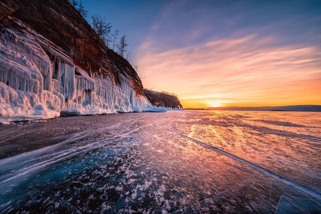 ロシア、シベリア、バイカル湖の凍った水の上に自然に砕ける氷と夕日の空。