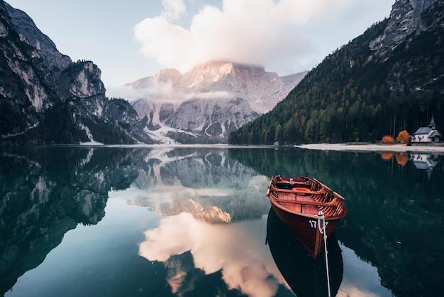 日没時間。背後に雄大な山のあるクリスタルレイクの木製ボート。水の反射。チャペルは右岸にあります