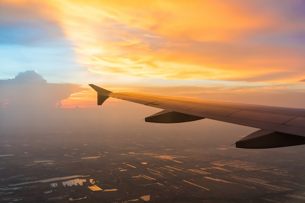Sunset in twilight time with wing of an airplane and cloud sky. photo applied to tourism operators.