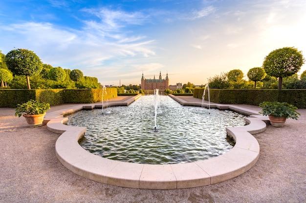 Вид на закат на дворцовый замок фредериксборк с красивым садом и фонтаном во время заката в хиллероде