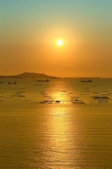 Вид на закат с видом на ко сичанг и грузовой корабль в море