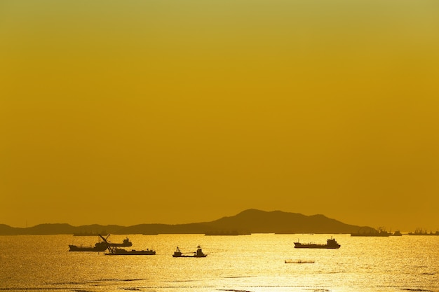 Sunset view overlooking koh sichang and cargo ship in sea.