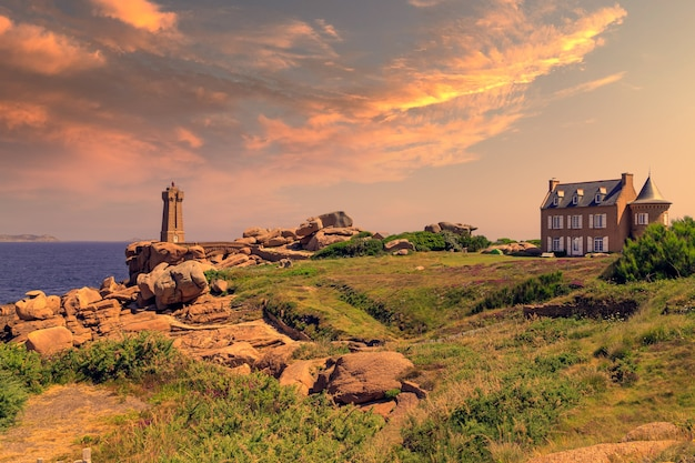Sunset view of the ploumanach lighthouse and surroundings in perros-guirec on the pink granite coast