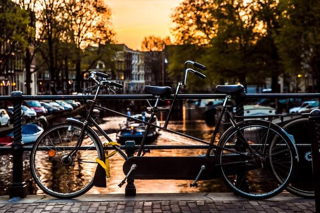 オランダ、アムステルダム市の橋、自転車、水の反射と夕日の景色