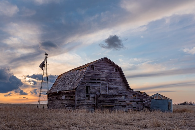 Sunset over a vintage wooden barn, bins and windmill in a saskatchewan, canada