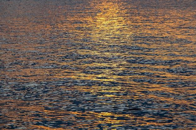 日没の水の背景、日没時の地表水、タイ。旅行と自然の概念。水上の黄金の夕日のテクスチャ、夕日の海の表面