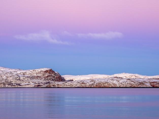 피요르드 위로 놀라운 마젠타 색상의 일몰. 테리 베르 카, 러시아. 겨울. 극지의 밤. 긴 셔터 속도.