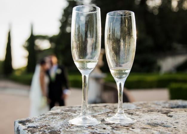 シャンパングラスと一緒に日没、背景に結婚したばかり