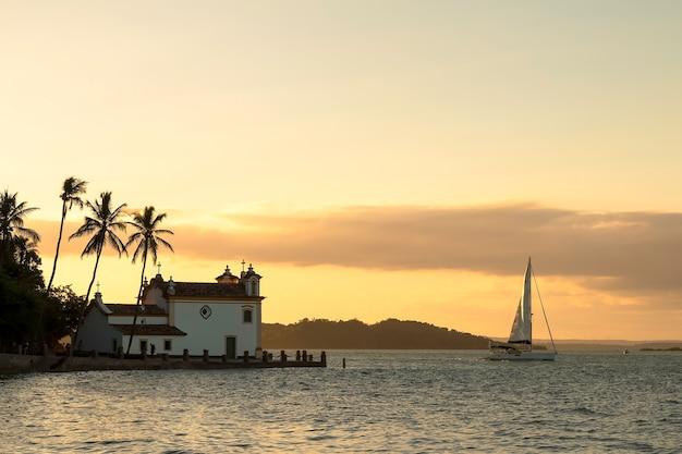 Sunset with church at todos os santos bay in bahia brazil.