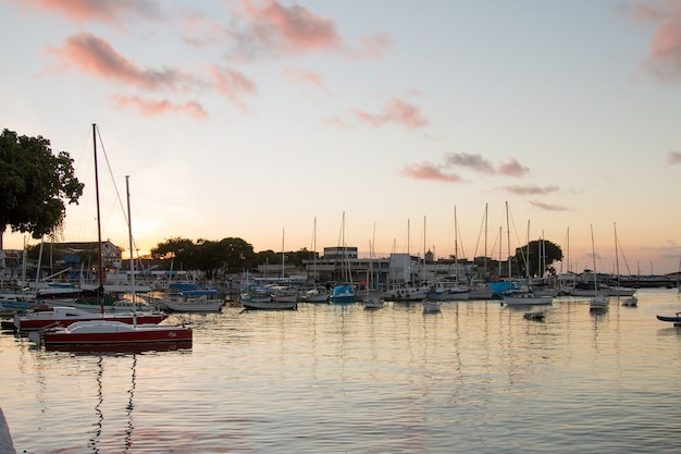 Sunset with sailboats anchored at the edge of the ribeira in salvador bahia brazil.