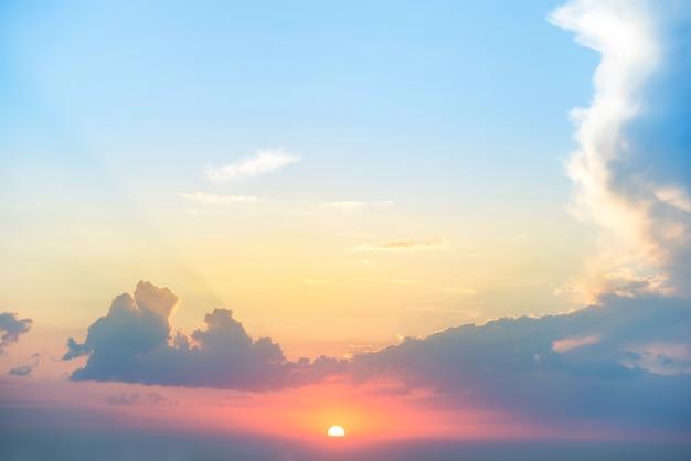 파란색과 주황색 극적인 하늘에 태양과 구름이 있는 일몰