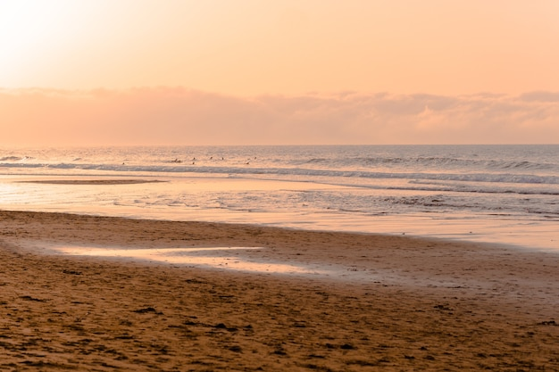 春の海でサーファーとの夕日。スペイン。休日